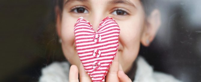 This is a picture of a little girl with a heart shaped little pillow in front of her nose and mouth.