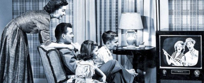 This is an old picture of a family in black and white sitting by a television set back in the middle 1950's.
