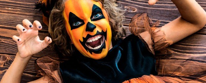 This is an image of a little girl with a scary painted pumpkin face making a growling expression.