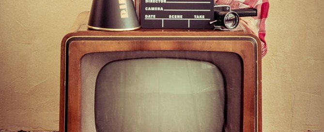 This image is a picture of a little girl standing behind a retro or vintage television.