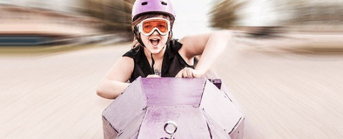 Young lady racing soapbox derby car.